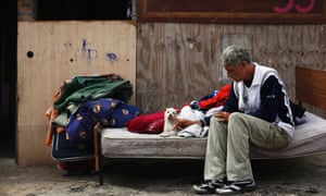 Giorgi Placintario caresses his nephew's puppy Leo as he sits next to the few belongings he was able to salvage before his shack was demolished in the shanty town settlement of El Gallinero, in the outskirts of Madrid, Spain.