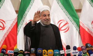 Iran's president-elect, Hassan Rouhani, waves during his first press conference