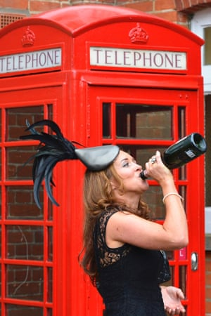 A racegoer makes sure she gets the last bit from the  bottle during the first day of the Royal Ascot horse racing festival.
