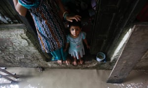 A child stands on the doorstep of her house next to an alley, flooded by the rising level of the river Yamuna after heavy monsoon rains in New Delhi. The rains are at least twice as heavy as usual in north-west and central India as the June-September monsoon spreads north, covering the whole country a month faster than usual.
