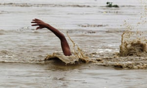 A man swims in the flooded river to retrieve floating watermelons.