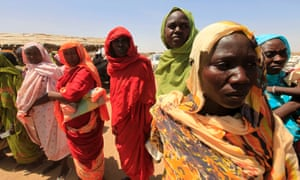 Displaced women wait to receive food at a distribution centre at Shangli Tobay village in North Darfur, as special envoys and diplomats arrive for a meeting to discuss the progress of a peace treaty.