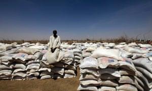 A man guards sacks of food at the distribution centre at Shangli Tobay village.