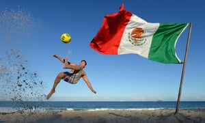 A Mexico fan jumps for an overhead kick on Copacabana beach in Rio de Janeiro, the day before Brazil play Mexico in the Confederations Cup.