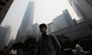 A Singapore office worker walks to work through smoke haze