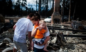 Brandy Burton carries her son Caiyleb Lewis through the rubble of her family's home that was completely destroyed in the Black Forest Fire in Colorado Springs, USA. Residents were allowed back into the area for a short period of time to view the properties that sustained the most damage from the fire. The Black Forest Fire, the most destructive wildfire in Colorado history, has destroyed 502 homes and charred more than 22 square miles.