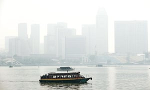 A boat sails along the Marina bay, Singapore, in front of buildings blanketed by haze
