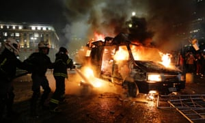 Firefighters work to put out a burning vehicle set on fire by protestors in Sao Paulo, Brazil as protests continued overnight.