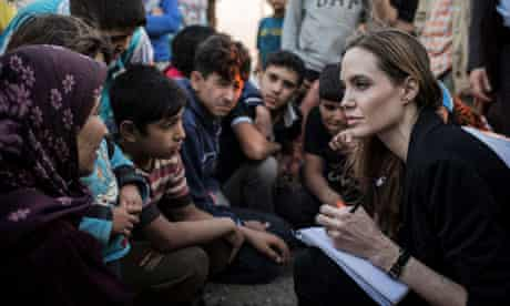 Angelina Jolie talks to to Syrian refugees in a camp on the Jordan-Syria border
