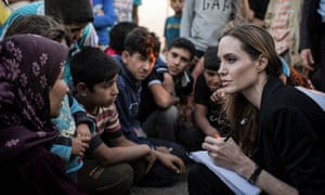 Angelina Jolie listening to Syrian refugees in a Jordanian military camp based the the Jordan-Syria border.