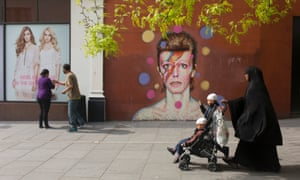 A woman with her children walks past the mural of iconic musician and singer David Bowie has appeared on the wall of Morleys department store in Brixton, Lambeth, south London.