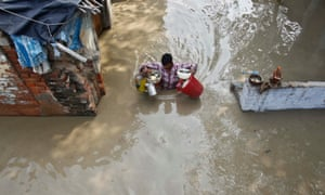 A resident carries his belongings through an alley flooded with the rising water level of river Yamuna after heavy monsoon rains in New Delhi, India. The rains are at least twice as heavy as usual in northwest and central India as the June-September monsoon spreads north, covering the whole country a month faster than normal.