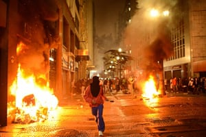 Brazil protests continue: A demonstrator runs as fires are started in Sao Paulo