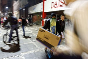 Brazil protests continue: Looters carry a tv sets out damaged shops in Sao Paulo