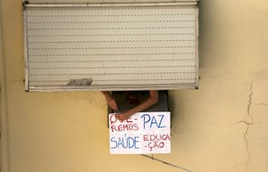 "Brazil protests continue: A person hangs a sign reading, ""We want peace, health and education"", outsi"
