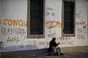 Brazil protests continue: A man sits in front of a wall sprayed with graffiti by in downtown Rio de J