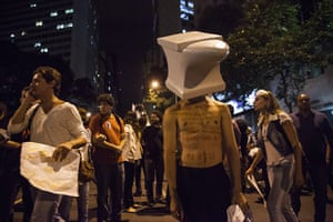 A man stands dressed with mock anvil on his head as thousands rallied in Ri