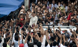 Aung San Suu Kyi waves to her supporters as she leaves the National League for Democracy headquarters where she celebrated her 68th birthday, in Rangoon, Burma. Suu Kyi has declared her intention to run for president.