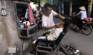 A cyclist rides past a street corner as barbers serve their customers at their open-air road side shop in Hanoi, Vietnam.