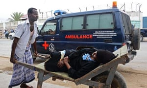 Aan injured woman is taken away after militants blasted their way into the UN base in Mogadishu