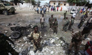 Somali government soldiers stand at the scene of a suicide bomb attack outside the United Nations compound in the capital Mogadishu. A suicide bomber and several gunmen attacked a UN compound in a strike that bore the hallmarks of al Qaeda-linked militants.