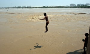 A man dives into the rising waters of the Yamuna river in New Delhi, India, swollen by monsoon rains.
