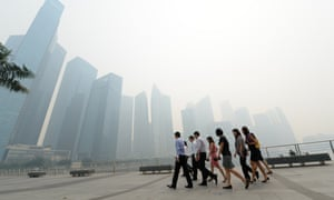 Office workers return from a lunch break in front of buildings blanketed by haze in Singapore. Air quality in Singapore hit its worst level for nearly 16 years as smoke from fires in Sumatra drifted across.
