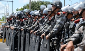 Anti-riot police officers block a street in Fortaleza, Brazil during a protest against corruption and price hikes and the current Confederations Cup. .