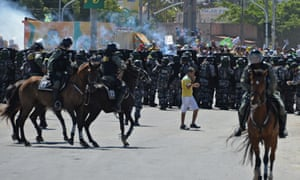 A football fan walks past as riot police officers clash with protesters who blocked access to the Castelao Stadium in Fortaleza, where Brazil is to play Mexico in a FIFA Confederations Cup Brazil 2013 football match.