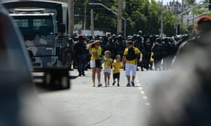 A family of football fans walk as riot police officers clash with protesters who blocked access to the Castelao Stadium in Fortaleza.