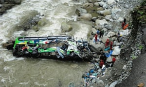 Rescue workers and authorities survey the wreckage of a crashed bus at in the Tarma river, Chanchamayo. Photograph: JULIO QUINTO/EPA
