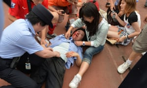 A police officer is treated for injuries after being crushed in a rush of fans to see David Beckham on his arrival at Tonji University in Shanghai.