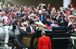 Ladies day at Ascot: Racegoers take photographs as the Royal carriage procession arrives at the