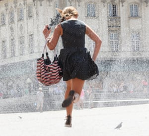 A girl jumps over a hose spraying water to cool off  at the Castle Square in Warsaw, Poland. Parts of Europe are currently experiencing a heatwave.
