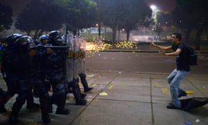 A demonstrator is shot by rubber bullets as riot police charge after clashes erupted during a protests in Rio de Janeiro overnight.