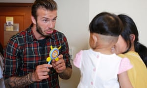 David Beckham pulls a few dad tricks as he plays with a child suffering from congenital heart disease during a visit to a hospital in Hangzhou, Zhejiang province, China.