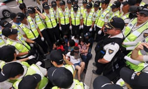 Outnumbered: policemen surround detained students who held a sudden demonstration in an attempt to march towards the presidential Blue House in central Seoul, South Korea.