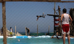 Men dive into a pool during a hot summer day at a beach in Gaza City.
