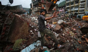 A resident gestures while searching for his belongings amid the debris of a collapsed residential building in Mumbra, India. At least nine people were killed and 14 injured when the building collapsed in the early hours on Friday.