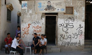 Palestinians smoke nargila as a poster depicting singer Mohammed Assaf is pictured on a wall of a ho