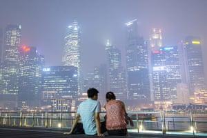 Singapore smog: A couple relaxes on the boardwalk along Marina Bay, with the skyline shroud