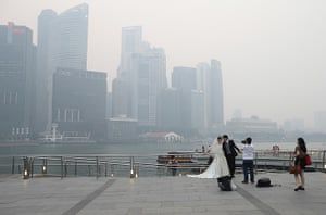 Singapore smog: A couple takes a pre-wedding photographs as the city skyline is filled with