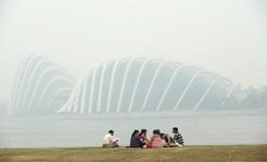 Singapore smog: A group of people sit along the bay as the Garden by the Bay's domes are sh