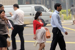 Singapore smog: A pregnant woman with a face mask walking on the street in Singapore