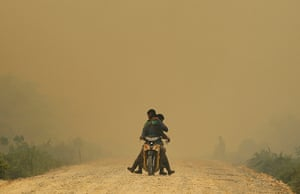 Singapore smog: Villagers ride a motorcycle in a haze hit Dumai, in Indonesia's Riau provin