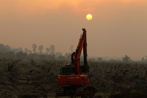 Singapore smog: A worker washes himself on an excavator at a palm oil plantation near Dumai