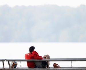 Singapore smog: A couple sits in a park near a river against a sky blanketed by light haze