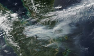 NASA Terra and Aqua satellite shows smoke caused by forest fires, indicated at source with red graphics, on the Indonesian island of Sumatra blowing east towards southern Malaysia and Singapore. Raging fires have choked Singapore with smog.