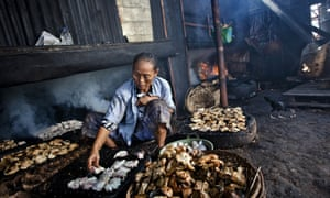 A worker cooks fish in a Bandarharjo smokehouse in Semarang, Indonesia.