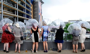 These ladies planned ahead. Racegoers shelter from the rain during day four of Royal Ascot.